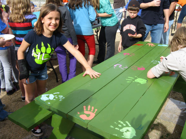 kids putting painted handprints on a table
