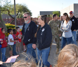 Veterans walking by school children welcoming them.