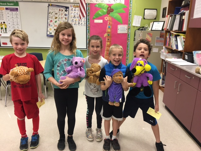 2nd graders showing stuffed animals they earned for reading over winter break.