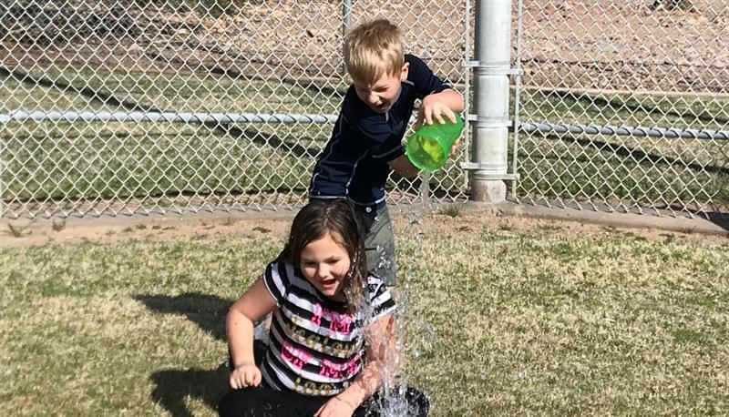boy pouring water on girl