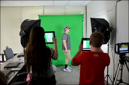Students using a green screen to create a video