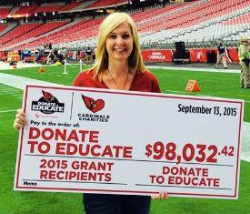 Paula Tseunis holds a check on Cardinals playing field