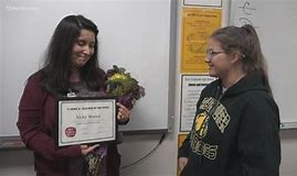 Mrs. Munoz receiving award from a student