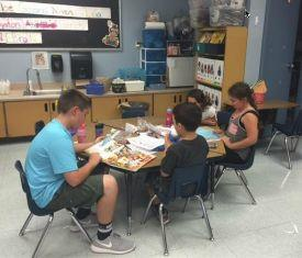 6th graders reading at a table with kindergarteners.